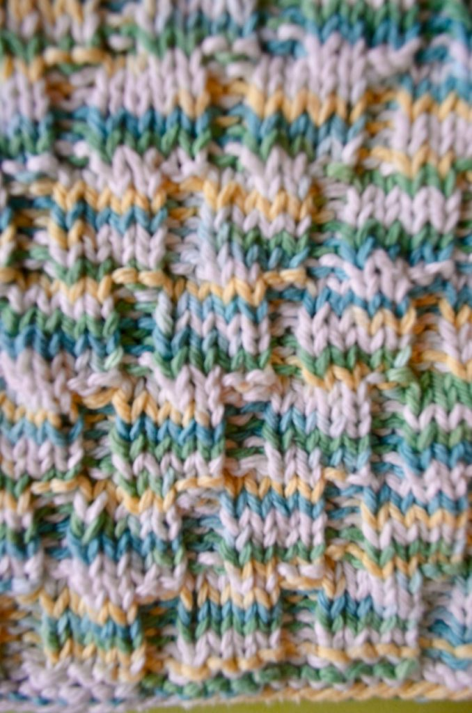 Knit ted dishcloth that looks like it has knit cables as the pattern , but it's only knit and purl stitches.