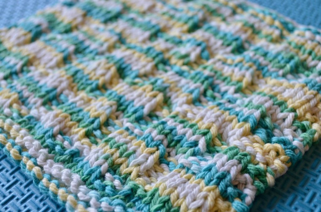 Knitted dishcloth that was taken at an angle to show details of the knit and purl stitches.