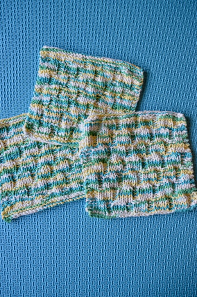 Three dishcloths on a foam mat that shows the mock cable knit pattern.